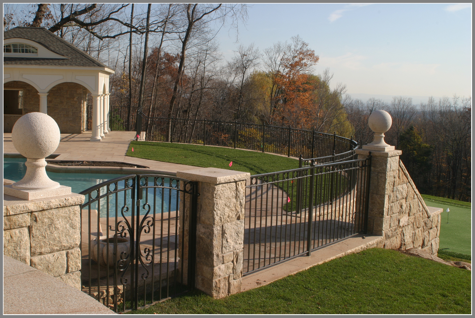 Wrought iron pool fence with stone columns by Artistic Outdoors