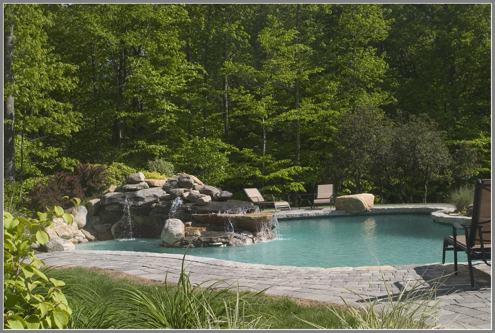 Swimming pool design with lagoon and waterfalls.