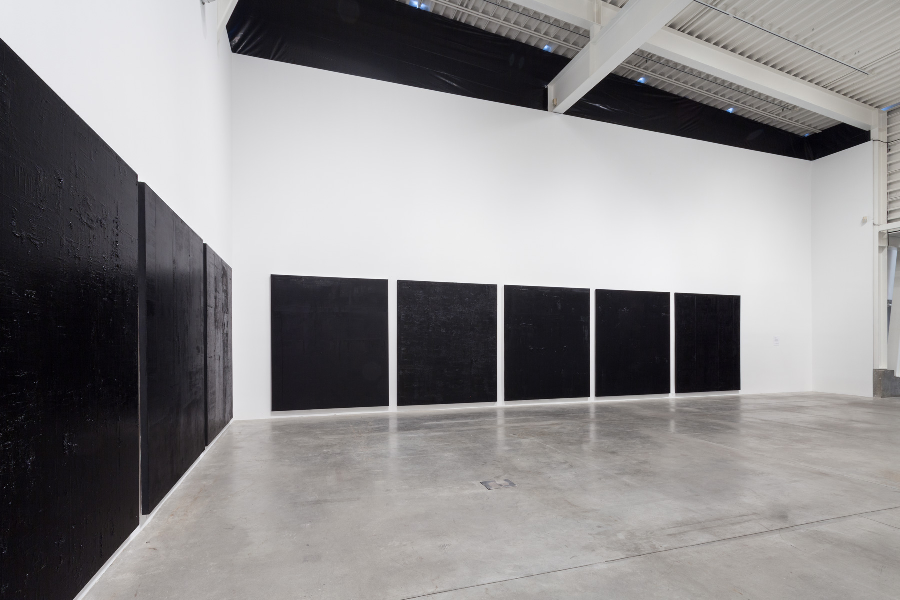 Morris and Helen Belkin Art Gallery, 2017. Untitled black monochrome paintings (3.-10.PBk9.CI77267/PBk11.Fe3O4) The Frequency 10 series. Oil, grit, graphite on canvas, each 213.36cm x 182.88cm (84 inches x 72 inches).