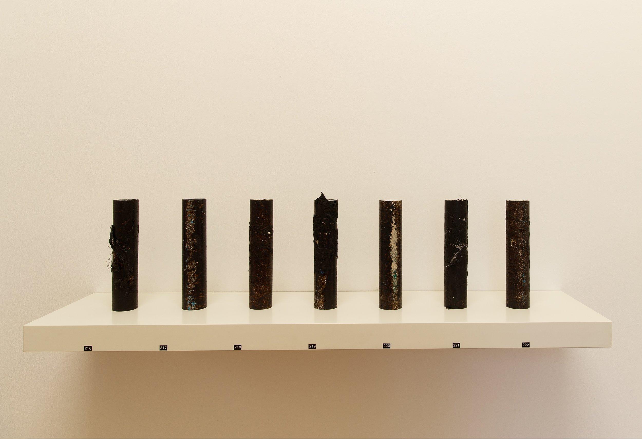 Remains # 1 - 7   bitumen rubber, detritus on PVC pipe  22.5 x 4.8 x 4.8 cm each  Photograph James Field, courtesy Adelaide Central School of Art