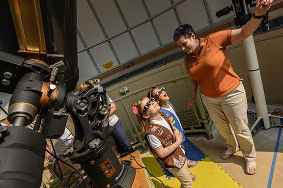 Girl Scouts marvel that they can look directly at the sun from the observatory at the McAuliffe-Shepard Discovery Center in Concord, NH. The Discovery Center's Christy Roberts showed the Daisy and Brownie Girl Scouts how they could view the sun without hurting their eyes. (GSGWM/Alan Macrae photo, with thanks to the McAuliffe-Shepard Discovery Center)