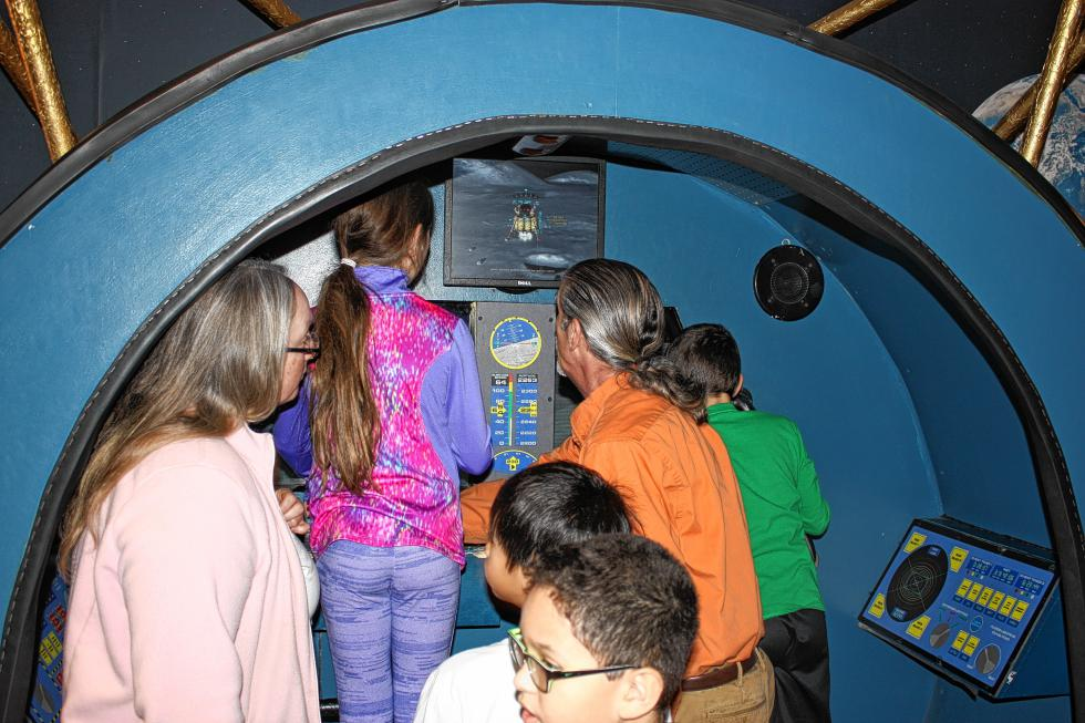 Discovery Center volunteer John Parodi (in orange) shows some Chichester Central School students the moon lander simulator. (JON BODELL / Insider staff)