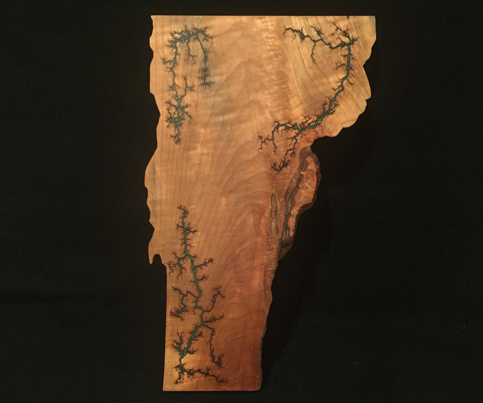 Lichtenberg Boards - This Vermont-shaped serving board is made out of hard maple sourced from none other than VT, and features a Lichtenberg figure etching done with 12,000 volts of electricity. The etching is then inlayed with crushed chrysocolla stone, and sealed with epoxy. The entire piece is then sanded to a glass like finish and coated with beeswax and mineral oil, making this serving board ready to be used. These are currently available at the Burlington Farmer's Market, the Champlain Islands Farmer's Market, in our online store, or by special order.