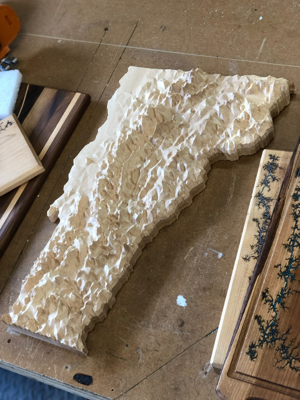 "Vermont Topographic Map - Carved using USGS satellite information, this solid maple map of Vermont measures 13"" across and 20"" long. The map was made on Kyle's purpose built CNC router, and took 20 hours to carve. It is incredibly accurate, however the elevations have been exaggerated by approximately 90 times to make the topography more pronounced."