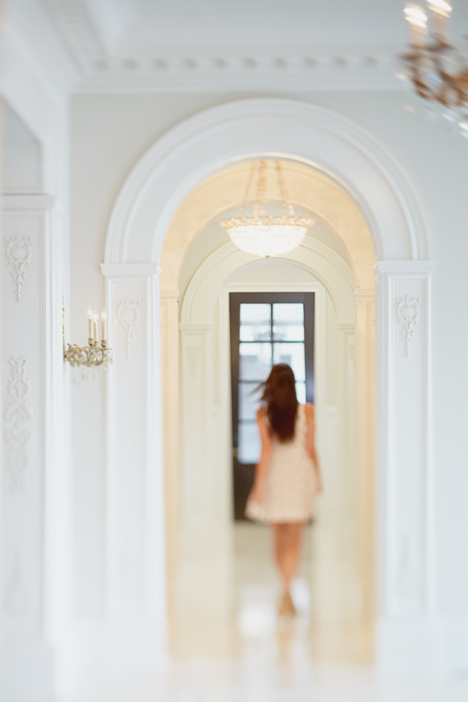 Stacey Van Berkel Photography I Lovely woman walking through archway I White on white I Elegance + glamour I Bernhardt Furniture