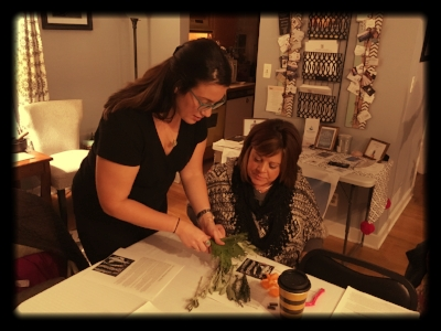Tatiana helping a guest make their own smudge stick at Spirit Tree Connections.