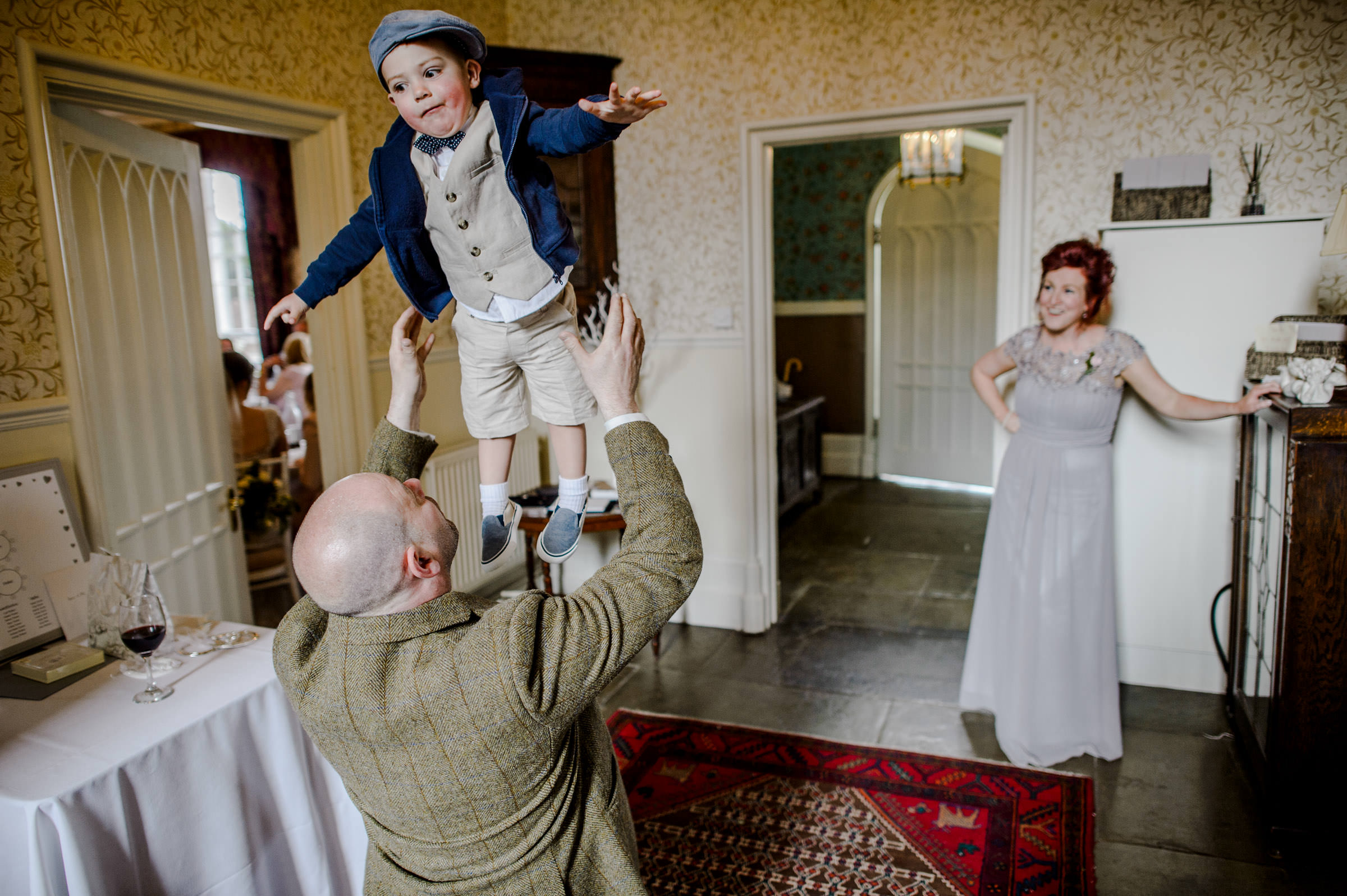 wedding photo of an usher throwing a pageboy up in the air.jpg