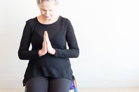 85037793-cropped-view-of-older-woman-with-short-grey-hair-and-black-clothing-sitting-on-yoga-stool-with-hands.jpg