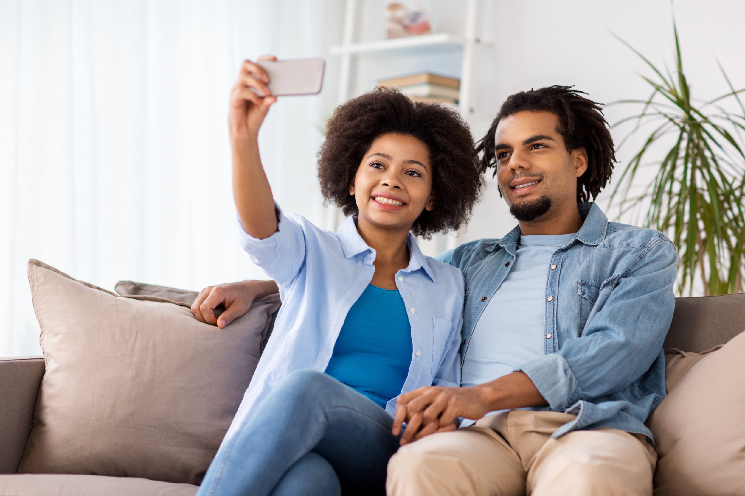 happy-couple-with-smartphone-taking-selfie-at-PYPVV8E.jpg