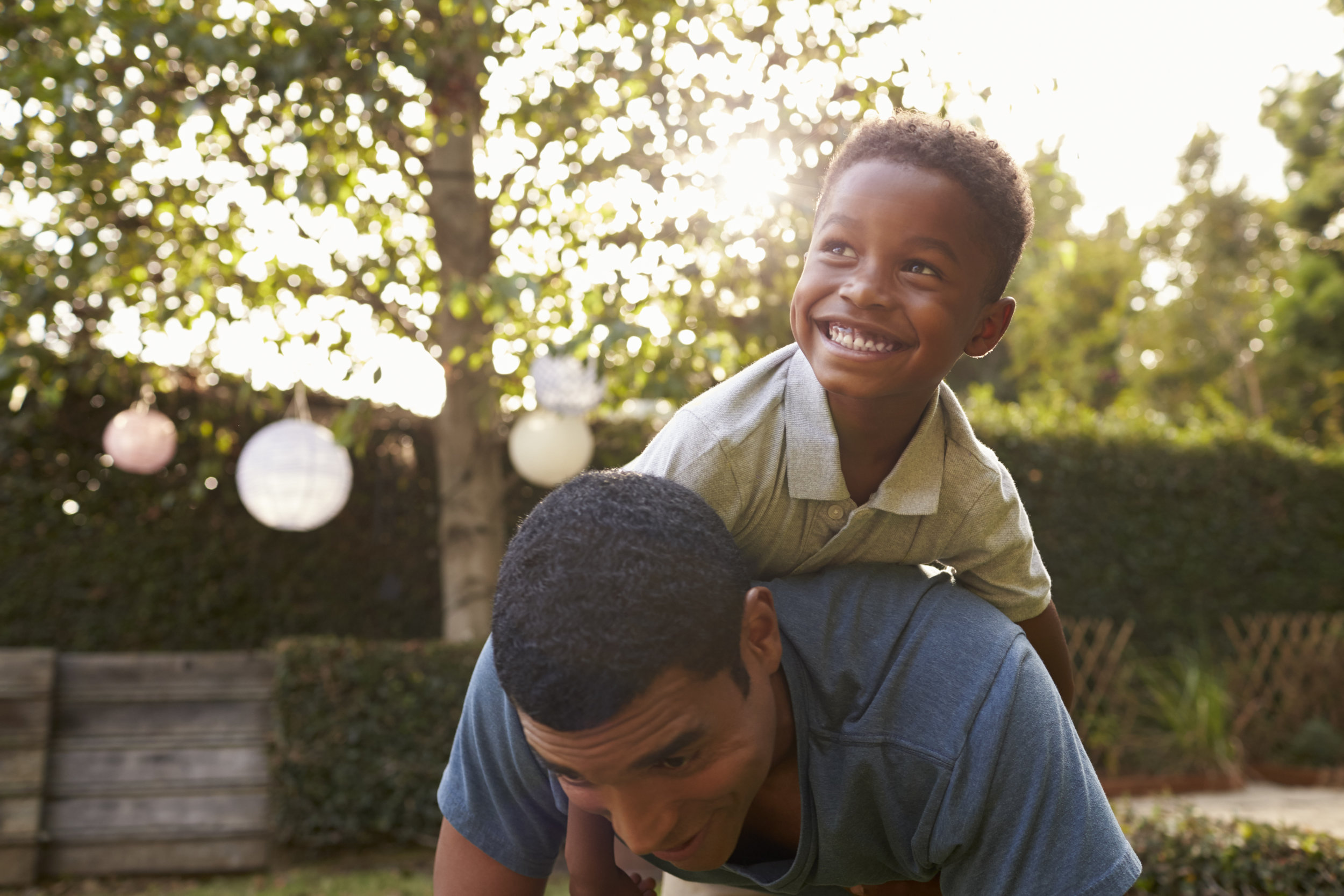 young-black-boy-playing-on-his-dad-s-back-in-a-PU7RN4X.jpg