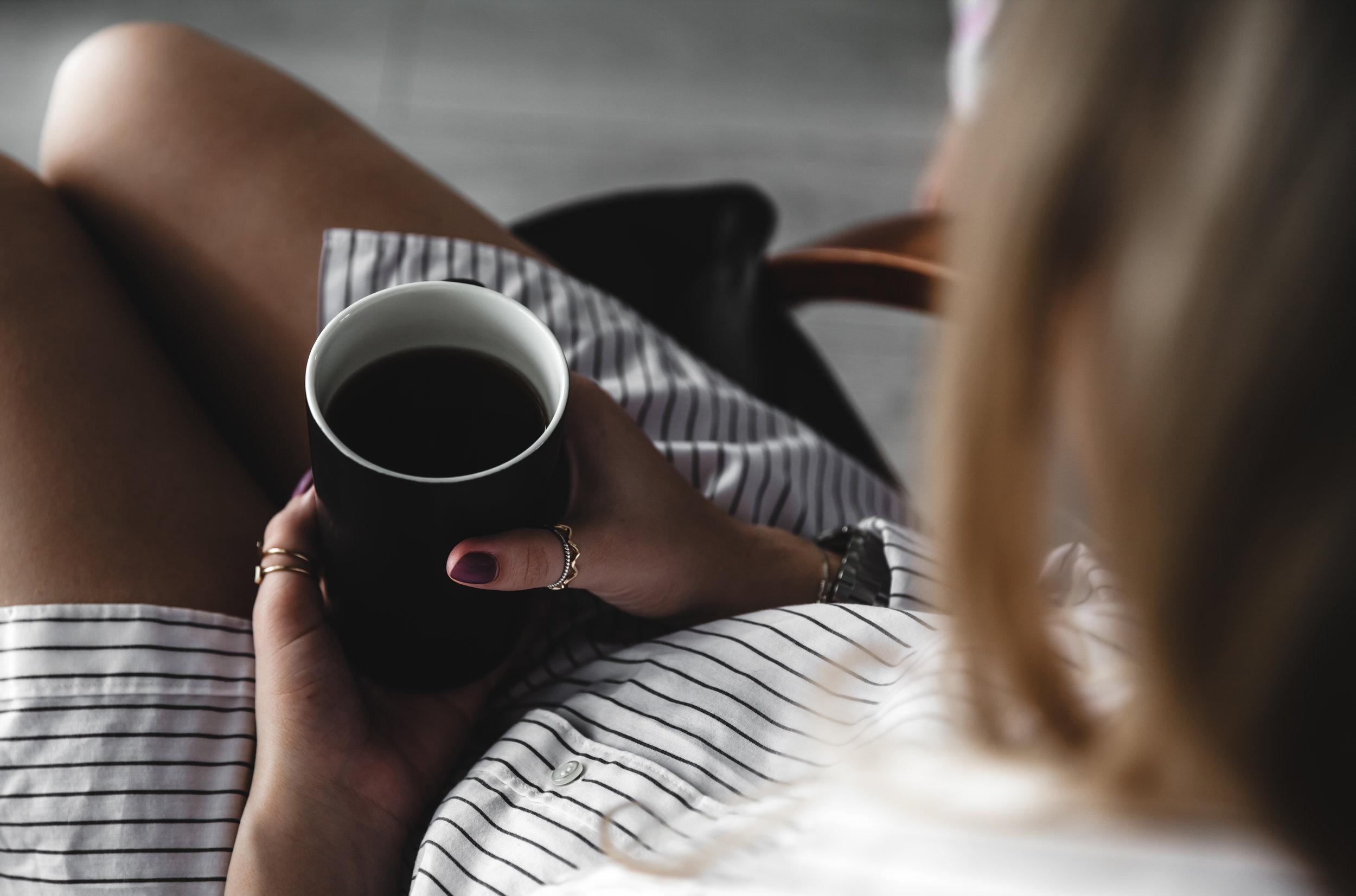 female-hands-holding-a-white-cup-of-tea-burgundy-73KTM5F.JPG