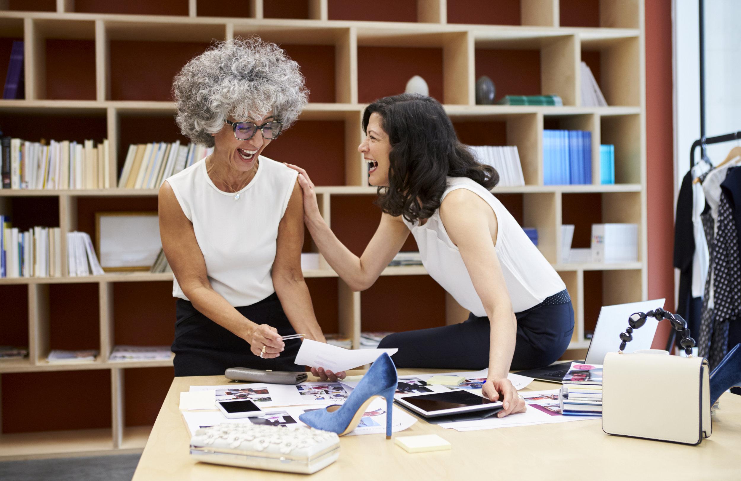 two-happy-women-talking-in-a-creative-media-PCA23WR.jpg