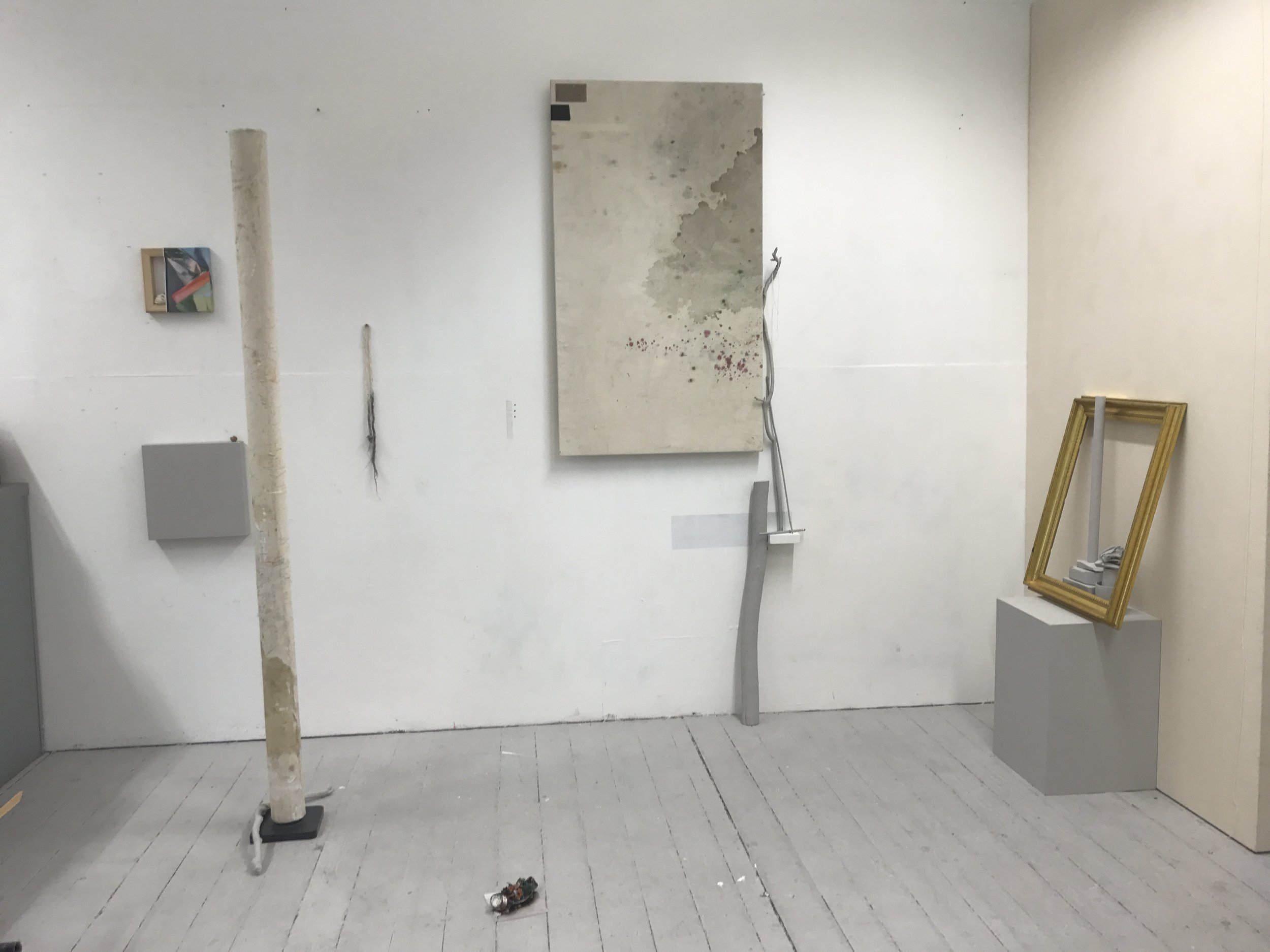Ally McGinn (2017) Studio view.  Final set-up for the week. My plan is to explore photos of this set-up over the weekend to decide on the final adjusments before crit on Monday.  EDIT - I changed a few elements, taking the two paintings on the left off the wall, I placed them on the floor. I added a pencil line on the wall and to  Reflection.  Which I think finishes the piece. I also added three drill holes to the wall, which look unintentional but are completely aesthetic.