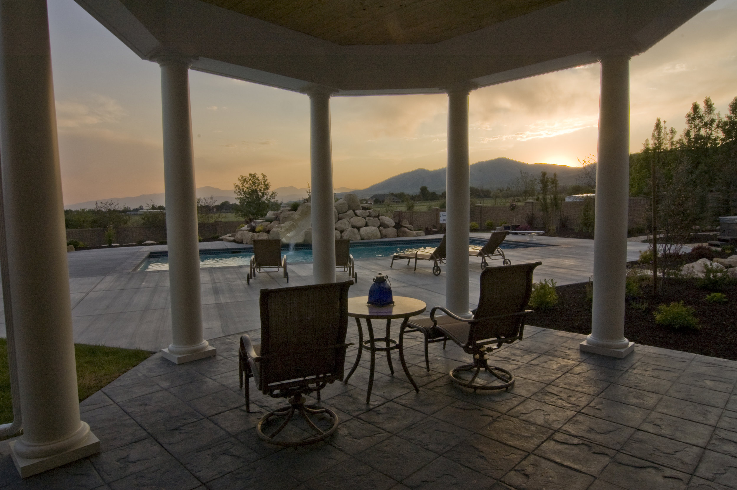 Patio and beautiful pool view with sunset.