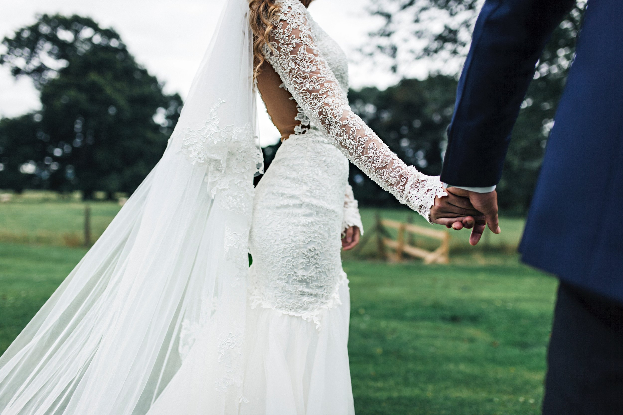 Lace Bridal Wedding Gown Holding Hands with Groom Veil Katie Laines Design and Coordination