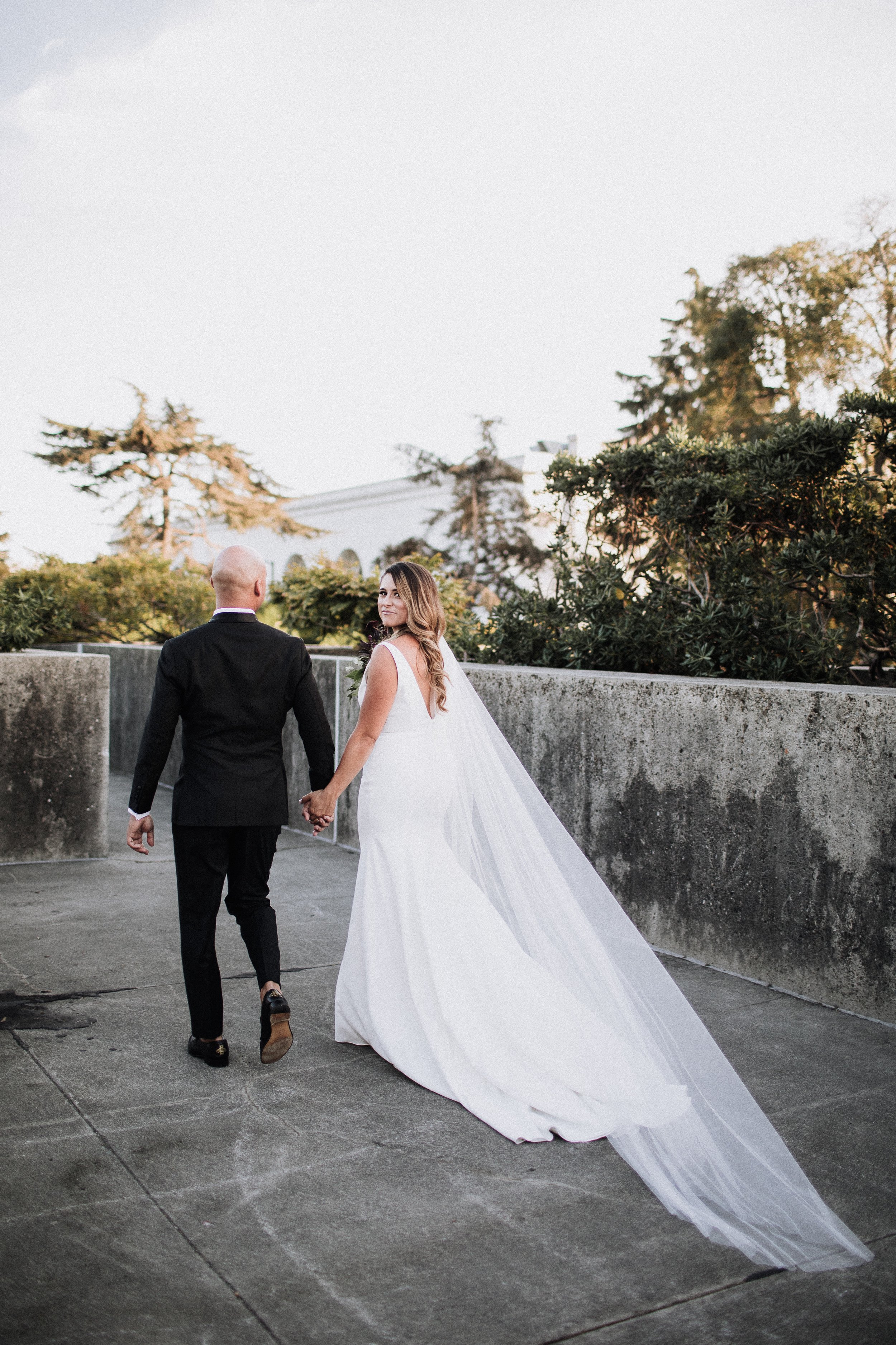 Bride and Groom Walking Holding Hands White Dress Long Train Veil Oakland Museum of California Katie Laines design and Coordination