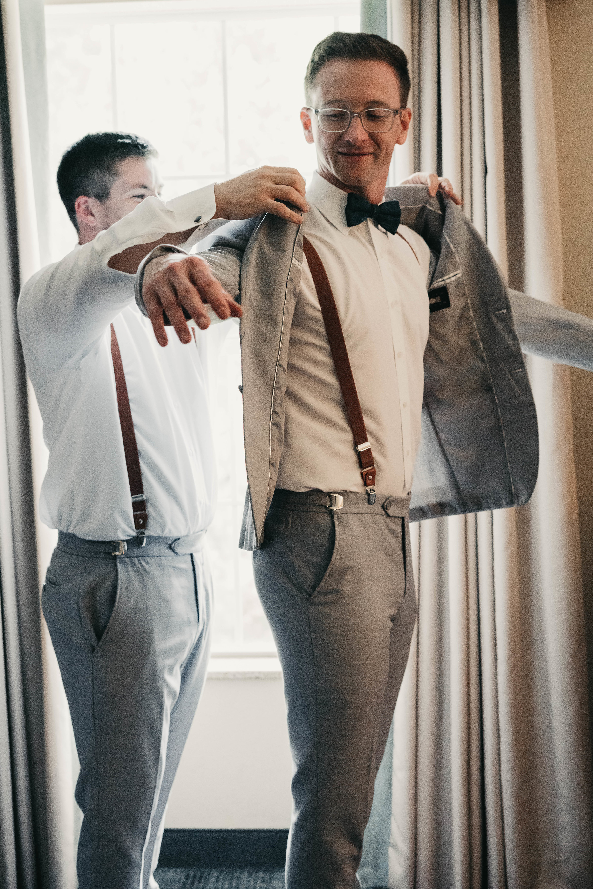Groom Putting On Grey Jacket