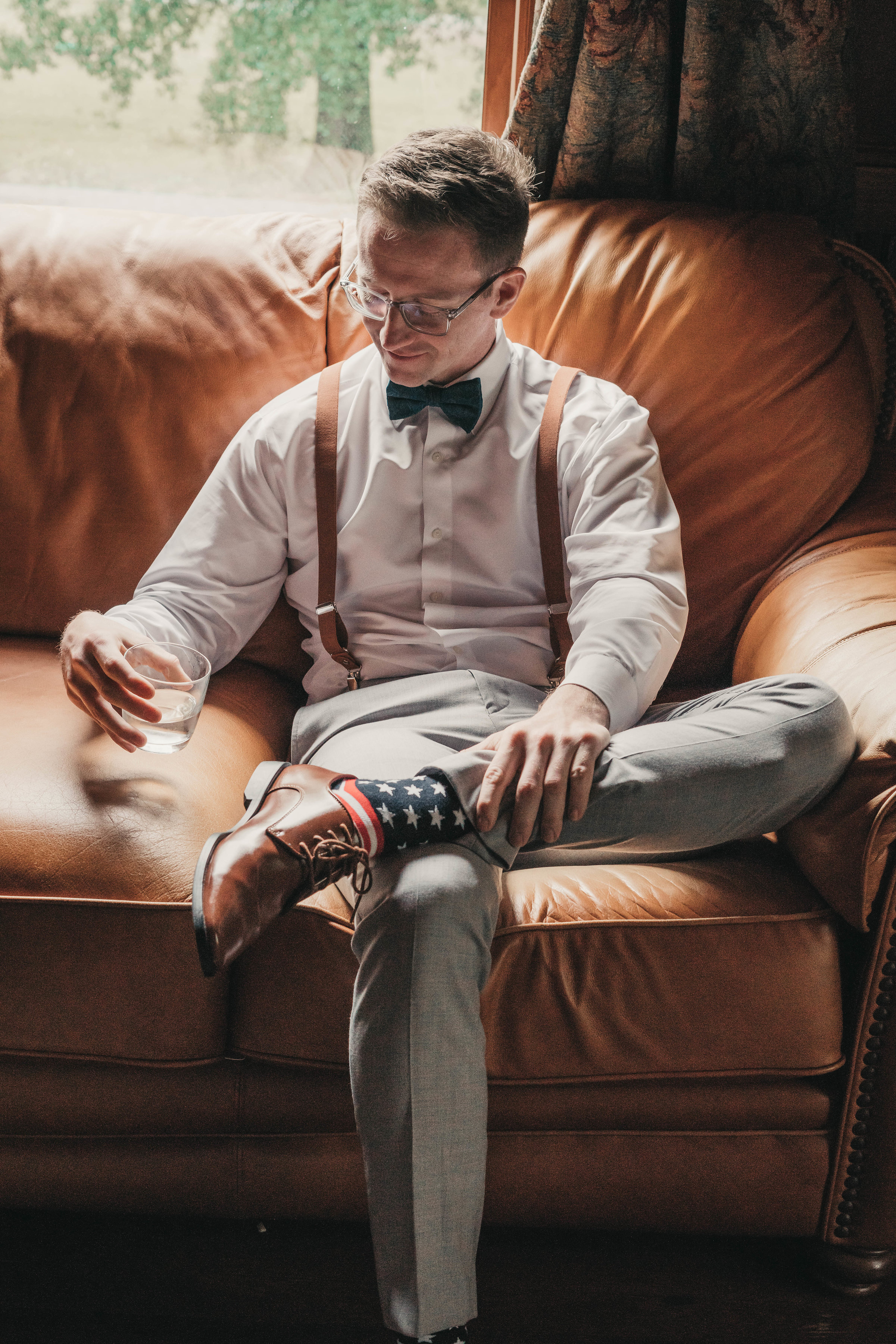 Cognac Leather Chair and Bourbon Groom Sitting Before Wedding