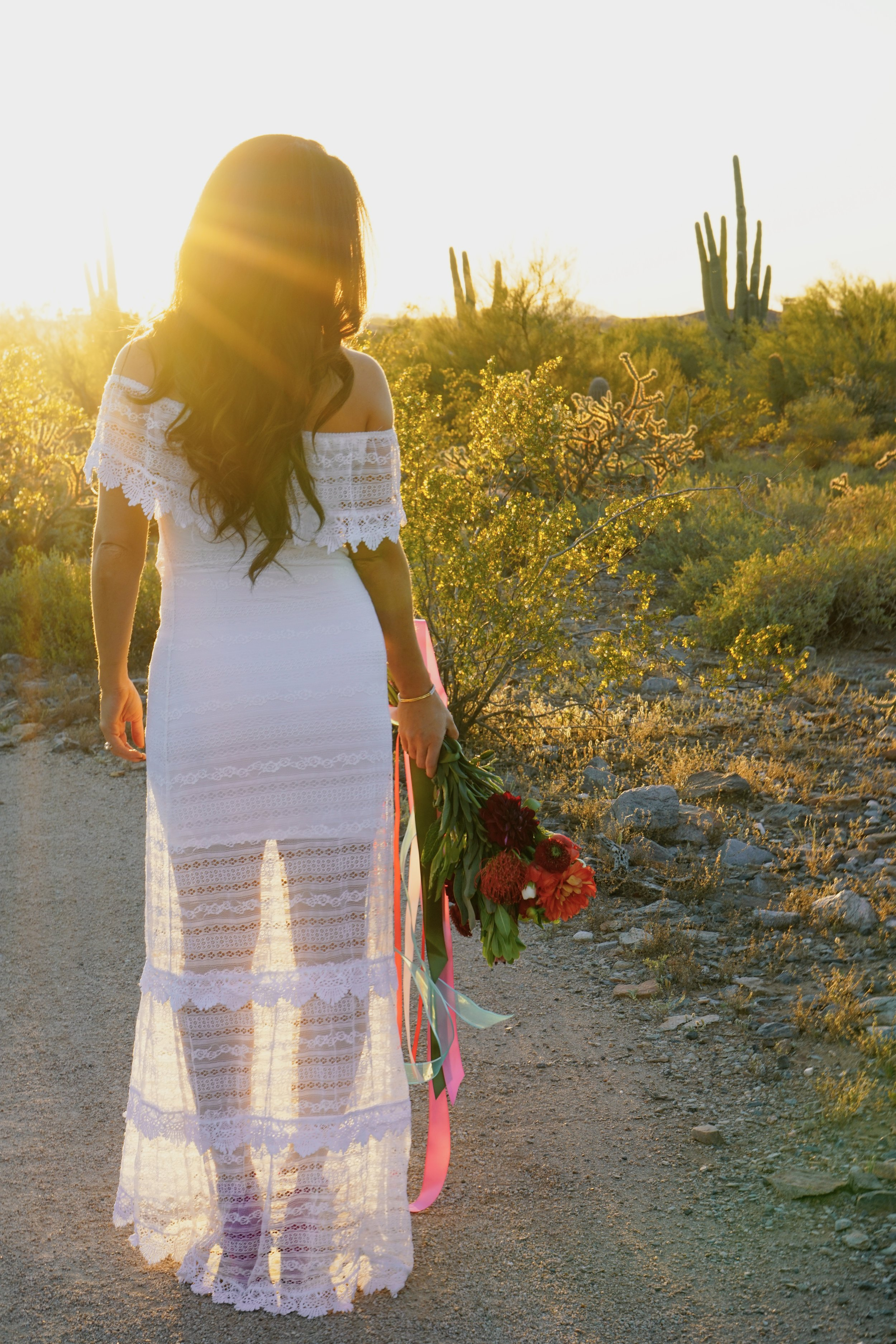 White See Through Gown on A Bride Holding Colorful Bouquet At Sunset in the Dessert