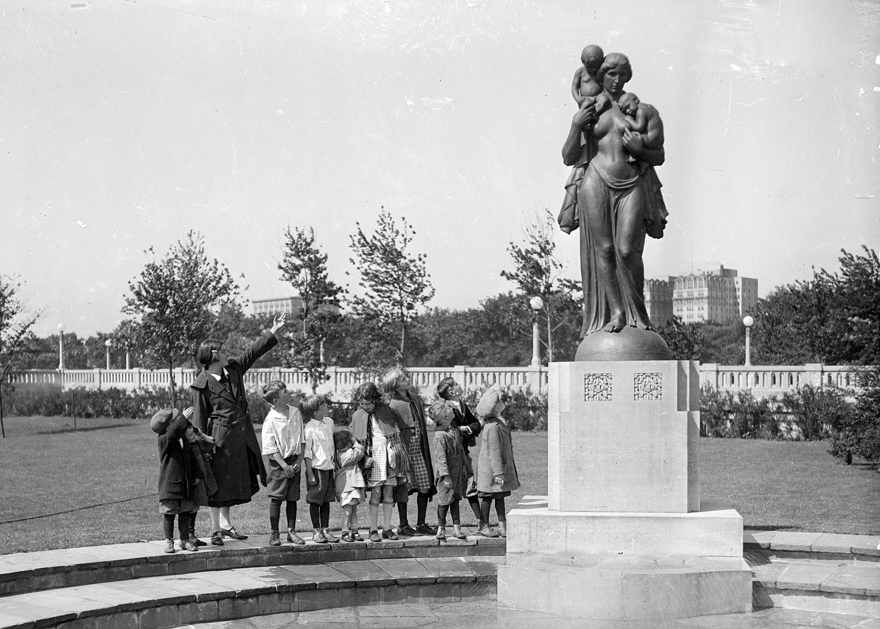 Woman and children standing along the edge of the original circular fountain, looking at  Charitas,  1925. Courtesy of the Chicago History Museum, DN-0079249.