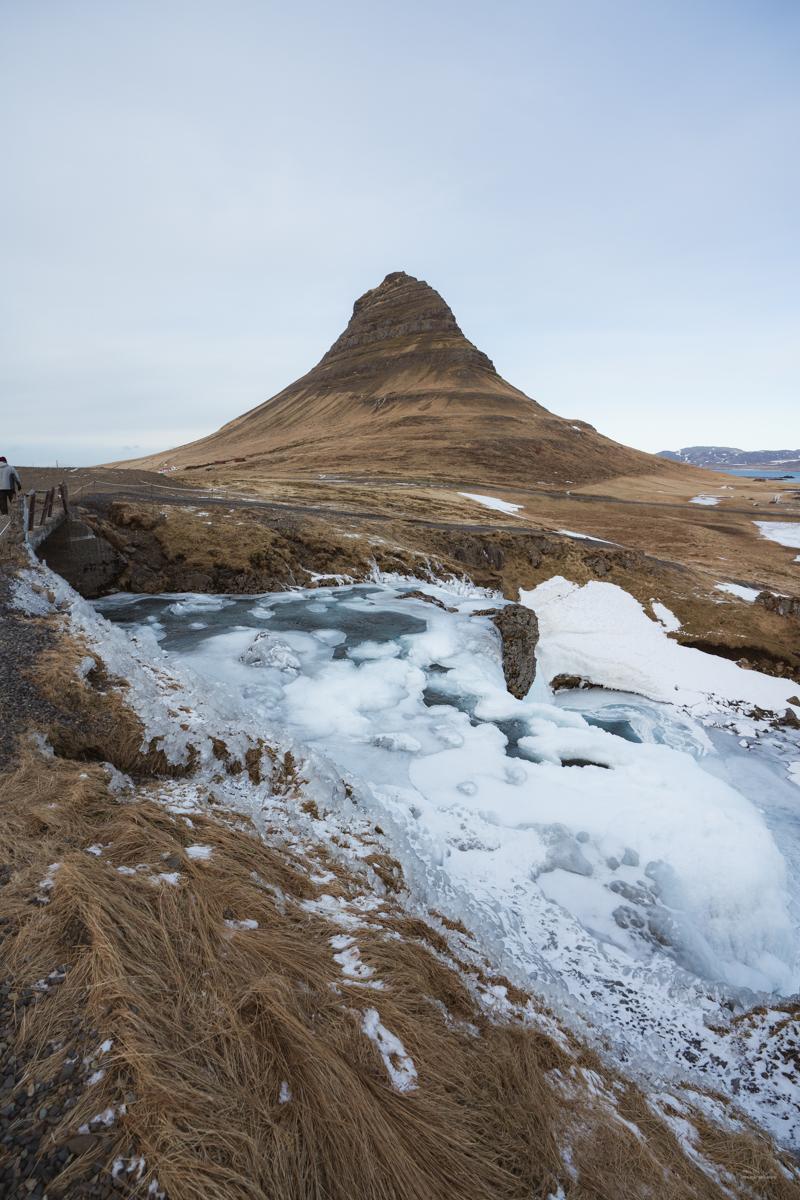 The frozen Kirkjufellfoss and the mountain of Kirkjufell