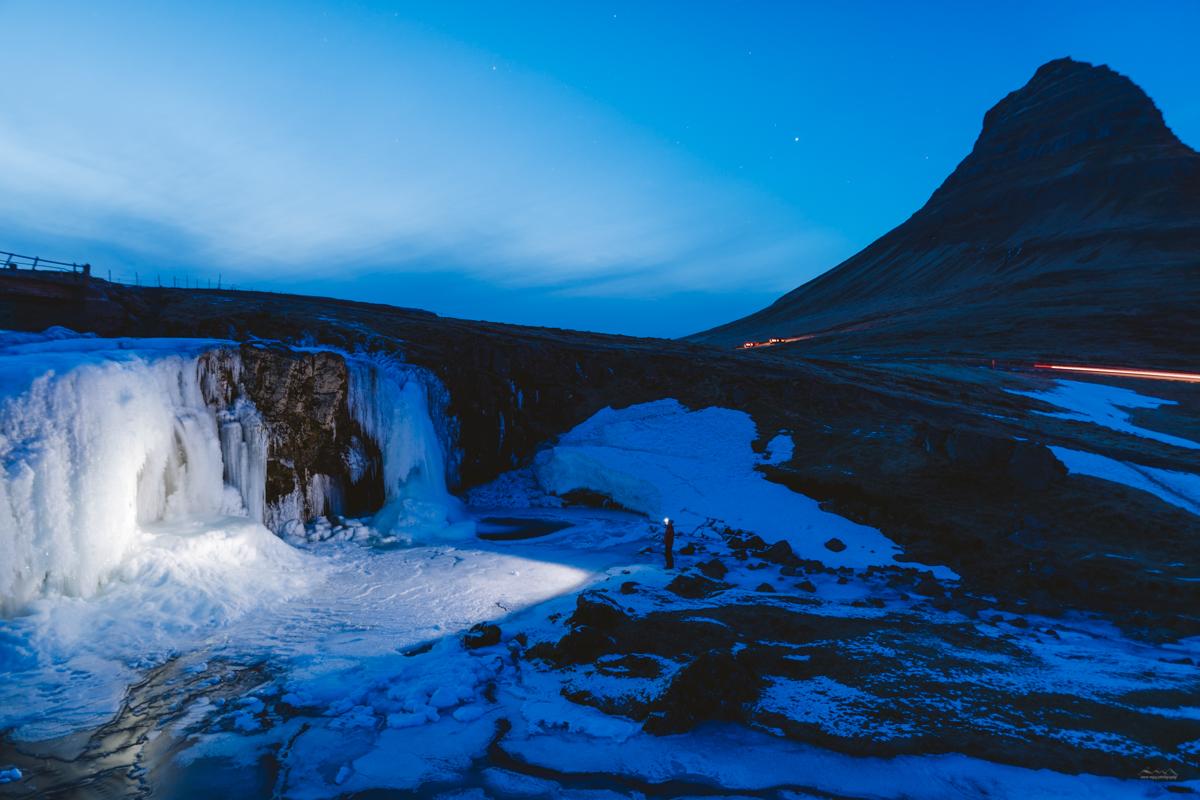 Walking on the frozen Kirkjufellfoss during blue hour