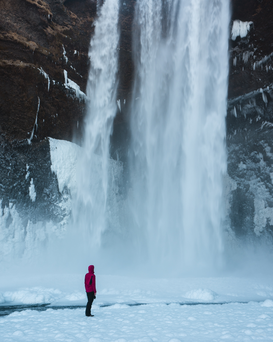 Man standing in front of the Skógafoss waterfall