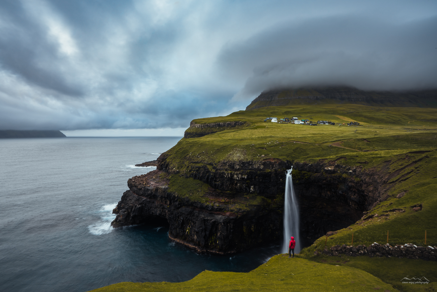 Man standing in front of Mulafossur Waterfall (Vagar Island), Faroe Islands