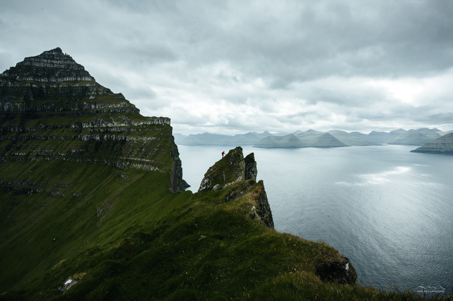 Man climbing the cliffs of Kalsoy, Faroe Islands