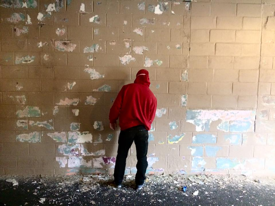 Trent Friesen scrapes paint off the north wall. His wife, Rachel, founded EMPAC Dance, one of our community partners.
