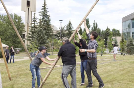 University students putting up a tipi with the guidance of an elder