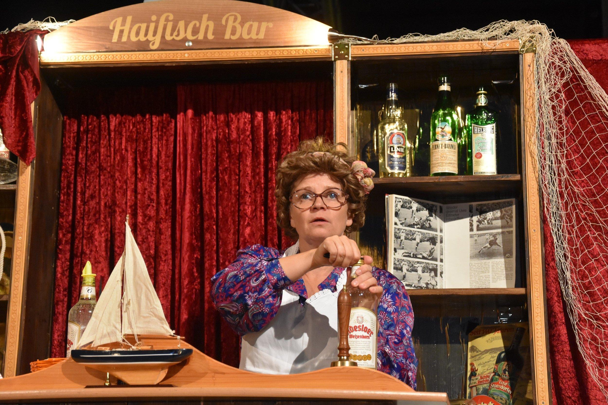 """""""Mord in der Haifischbar 1"""" - Hamburg-St. Pauli im Jahre 1965: In der Haifischbar wird gesungen, getanzt und gefeiert. Man findet in dieser Kneipe eine Rosenverkäuferin, Seemänner, leichte Mädchen, eine dicke singende Barfrau und zwielichtige Herren. Mitten in dem turbulenten Treiben wird der Zuhälter Danzinger erdrosselt. War es seine """"Freundin"""" Moni? Oder steckt etwa der Wirt Hugo dahinter? Und wieso schaut die Rosenverkäuferin so unschuldig? Gott sei Dank kommt Wachtmeister Lothar zur rechten Zeit in die Haifischbar."""