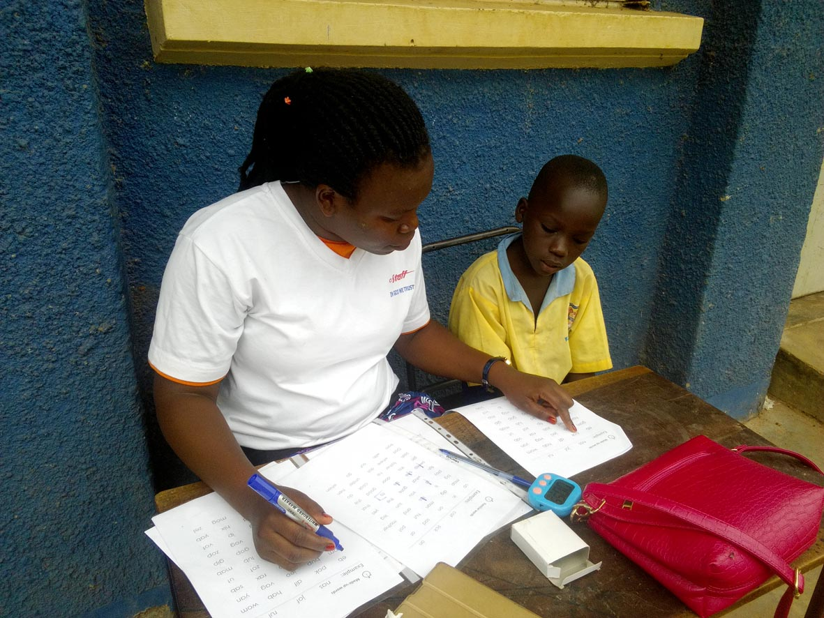 Teacher Diana from St Michael's Kindergarten and Primary assessing the reading of a pupil in Negri Primary School, Gulu.