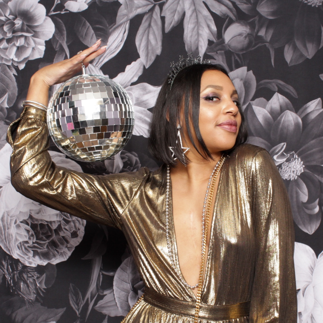 New Year's photo booth picture with black and white floral backdrop and woman holding a disco ball.