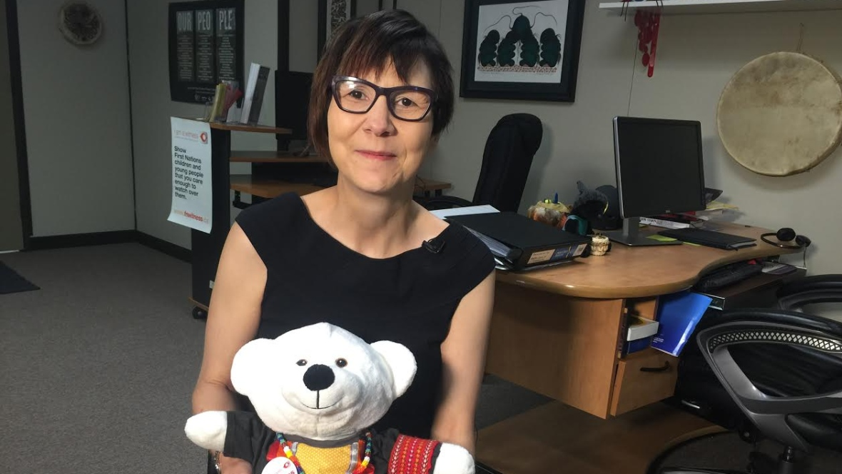 Cindy Blackstock, executive director of First Nations Child and Family Caring Society of Canada, is pictured in her Ottawa office with one of the organization's bear ambassadors.