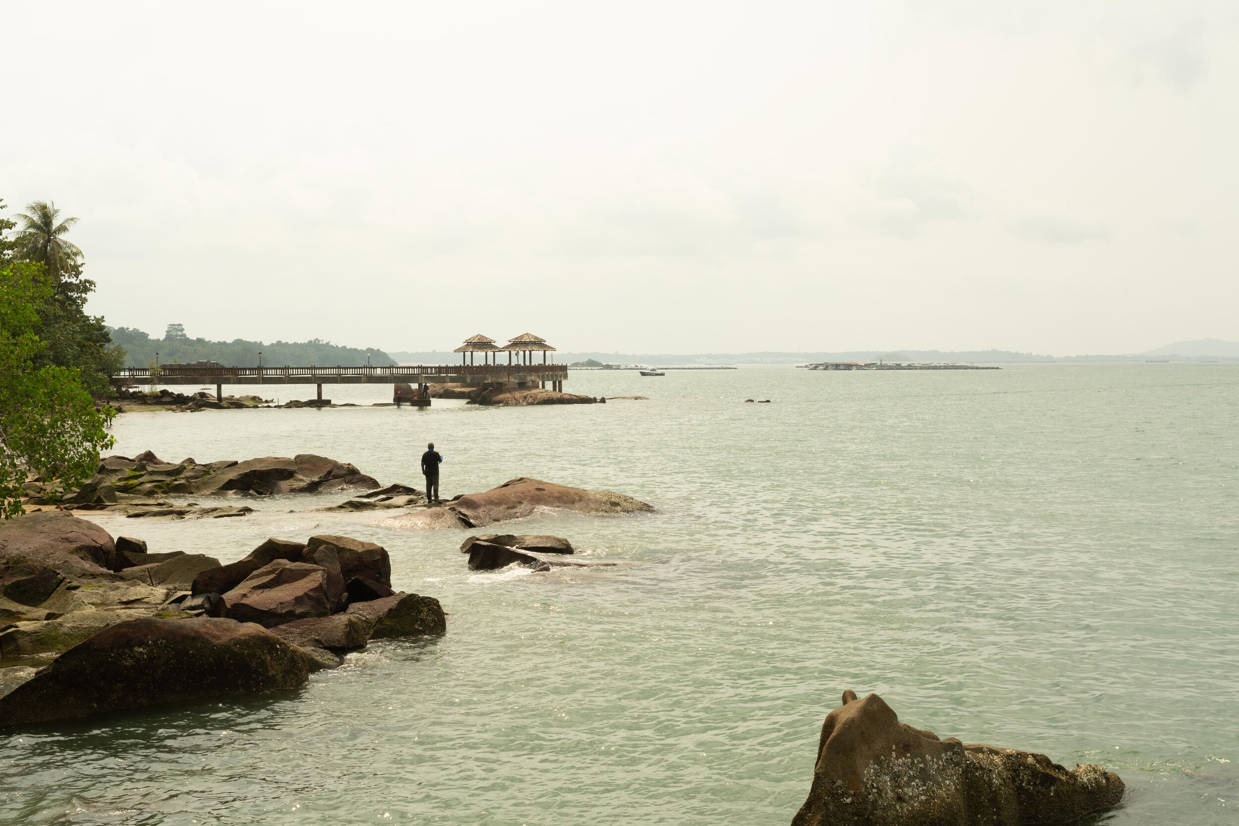Looking east from the island's main jetty, with the fisherman and stone prominent in the waters