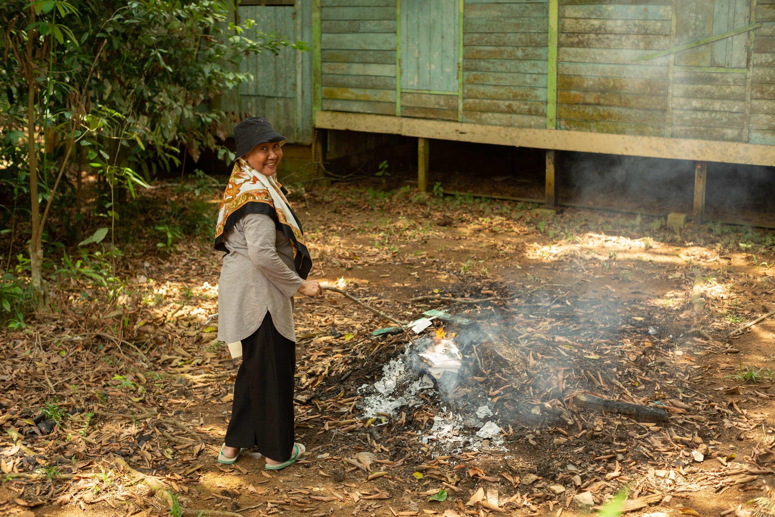 Cik Samsiah burning leaves and paper