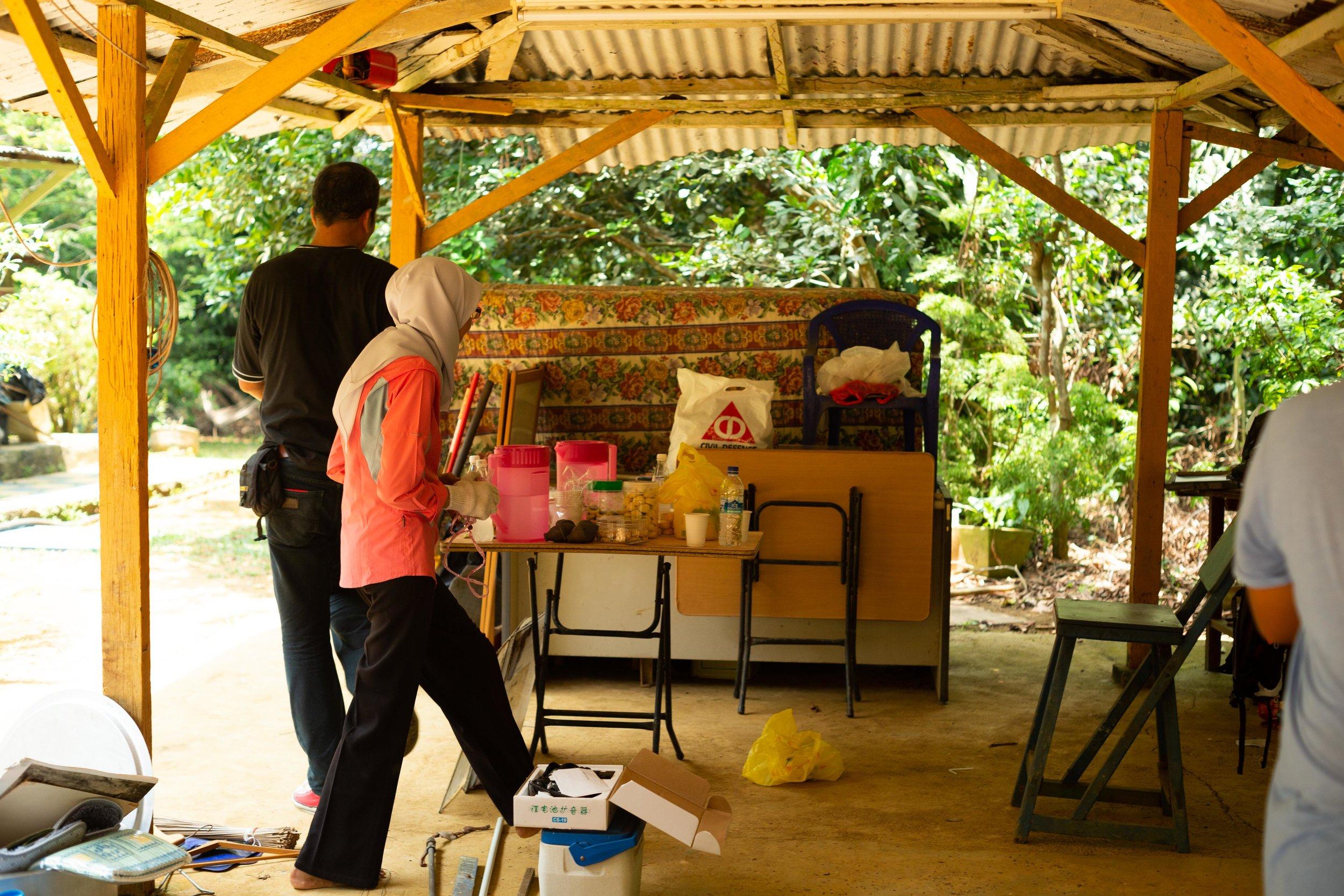 Cik Kamariah, resident of the Kampong, sorting through her belongings