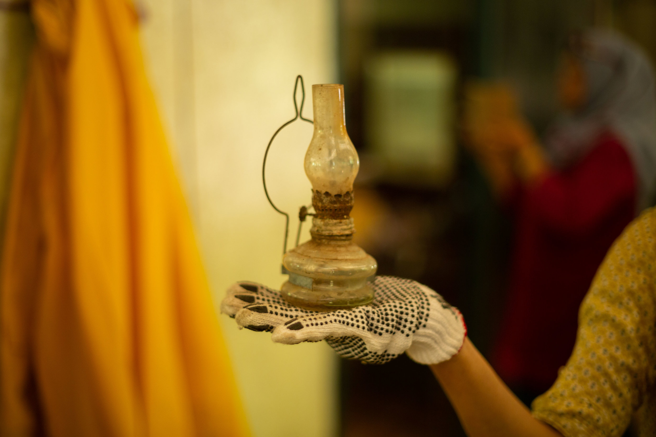 Cik Nora holding a 19th century kerosene lamp