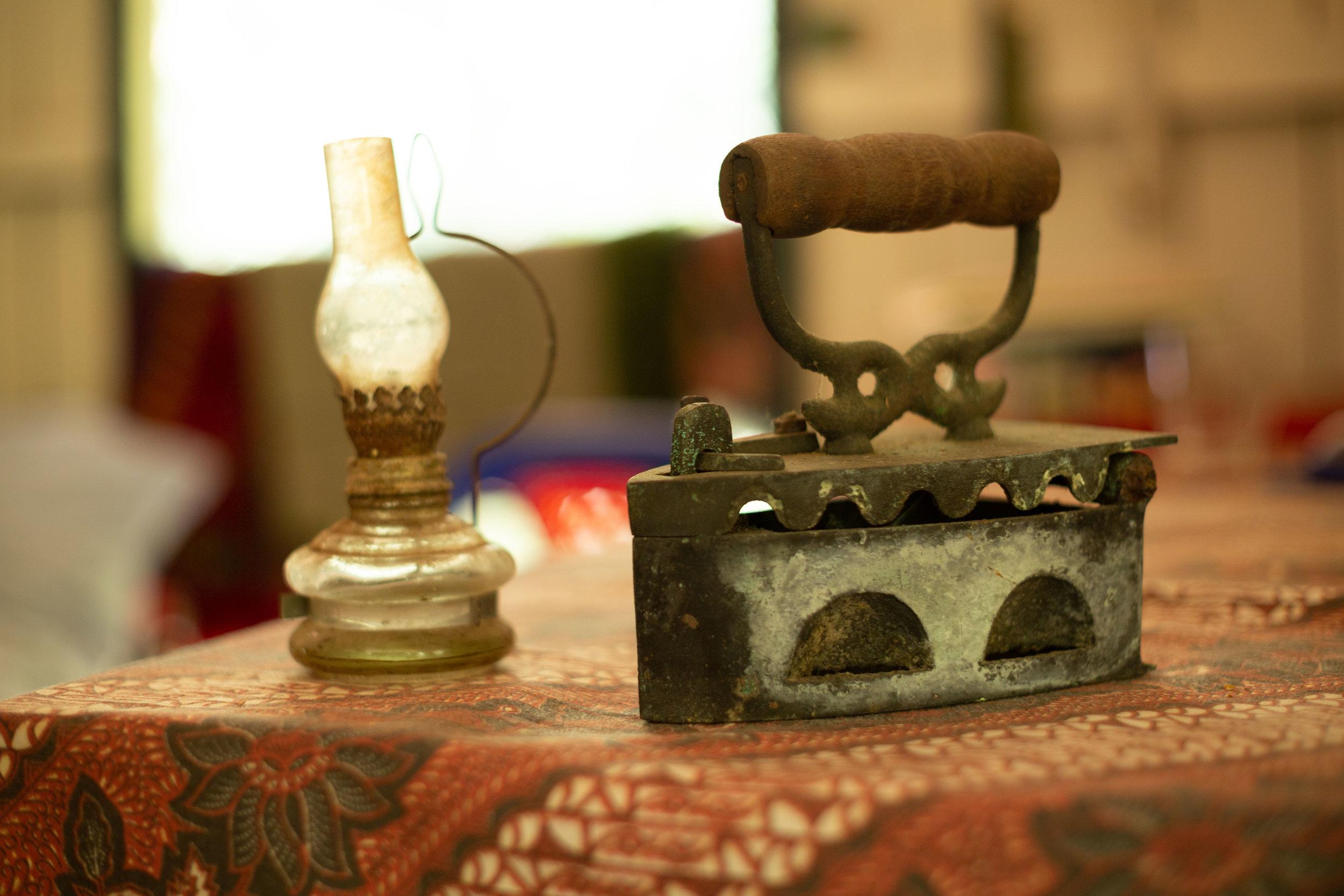 The 19th century kerosene lamp next to a coal-powered ironing device