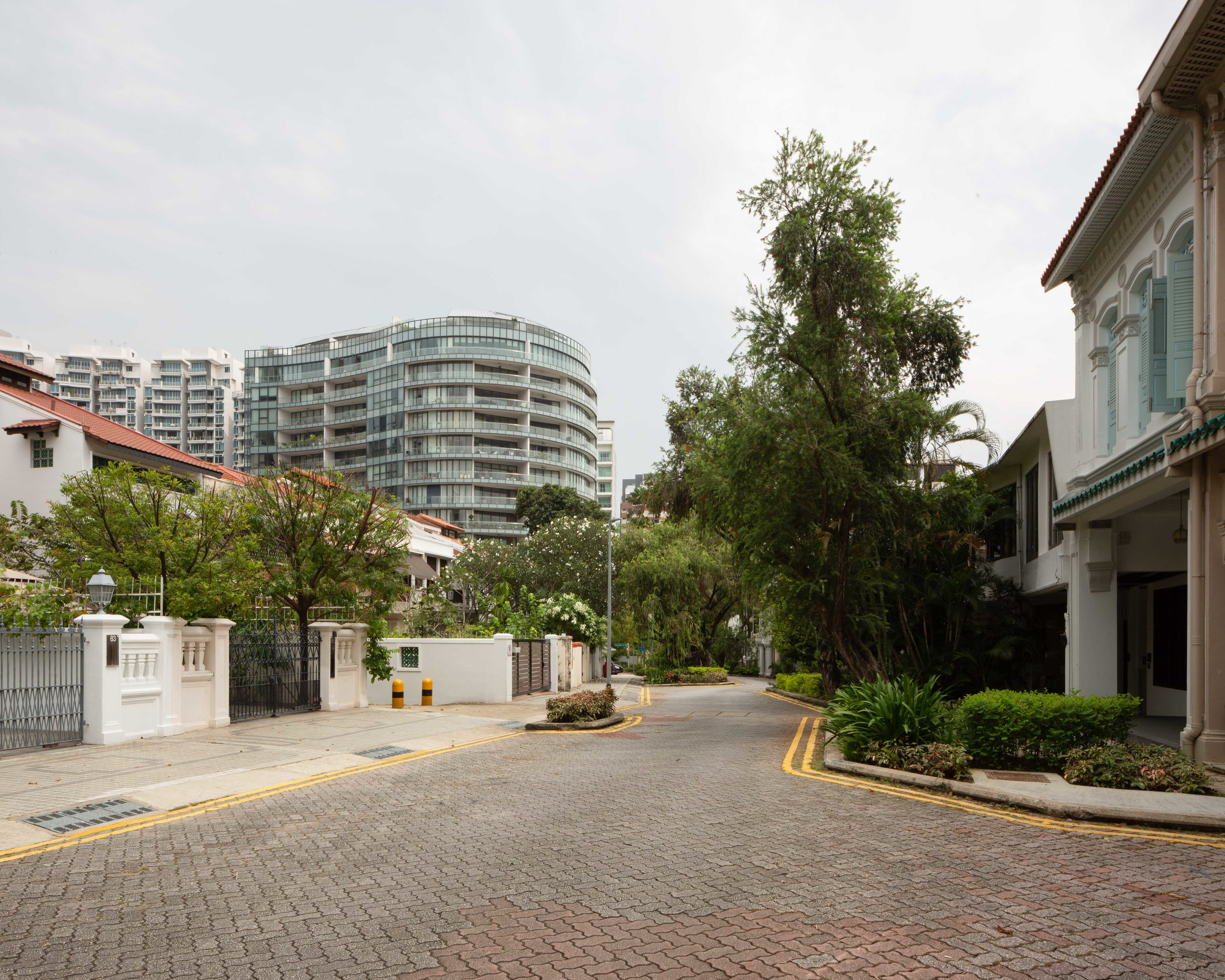 Looking down Emerald Hill Road with a glass-clad condominium in the background