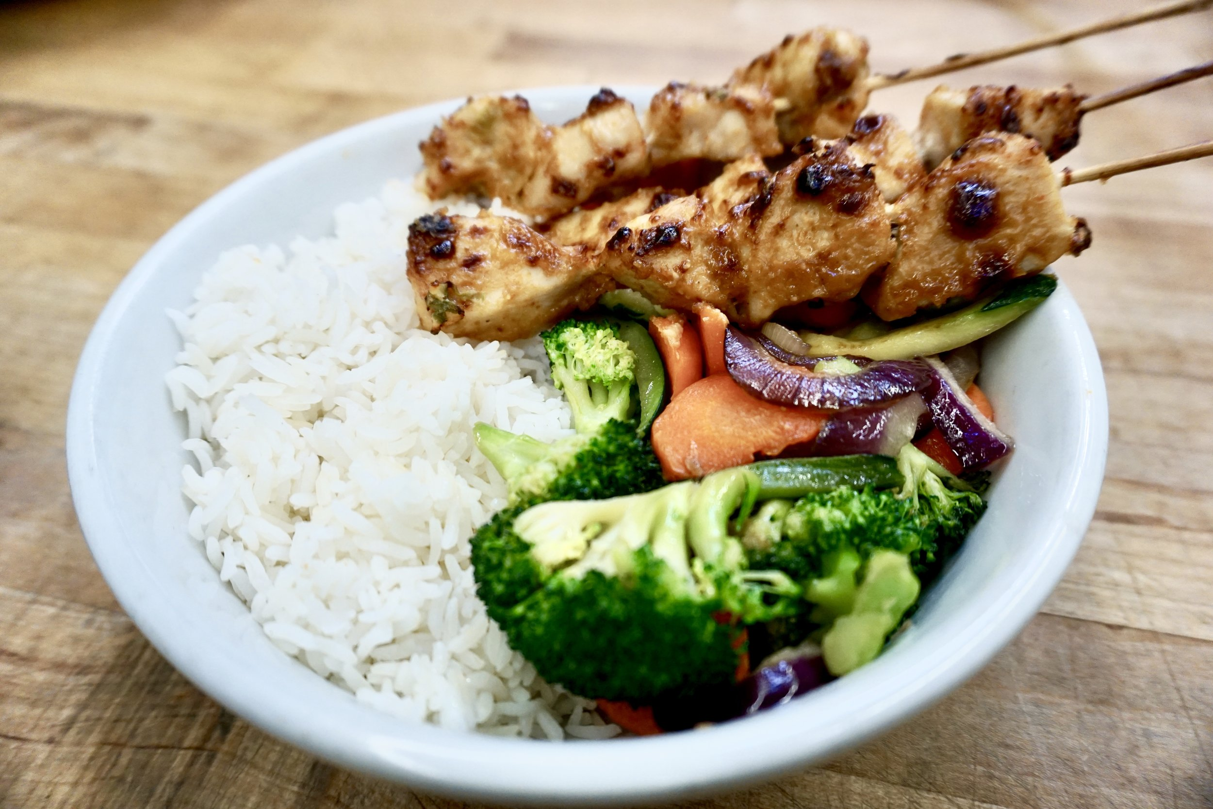 April Cafe Special - Check out our Roasted Peanut Satay Chicken Skewer Bowl served with seasonal vegetables over a bed of Jasmine rice available at all cafe locations.