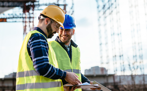 Two construction workers at a worksite wearing reflective vests discussing paperwork