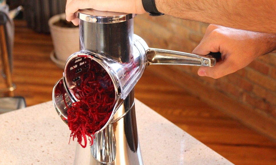 man using the HyCite Food Cutter to shred beets