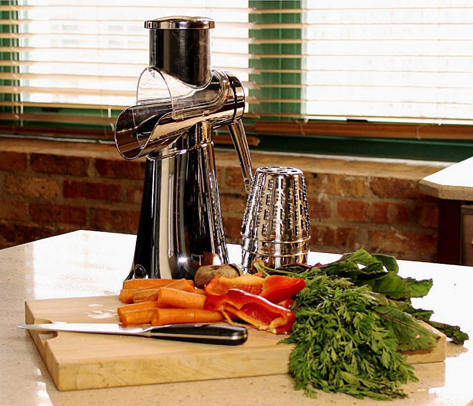 HyCite Food Cutter sitting on a kitchen countertop behind a cutting board covered in vegetables