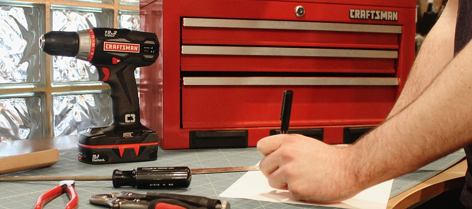 close up of a person working in a shop next to a Waterloo Craftsman toolbox and power drill