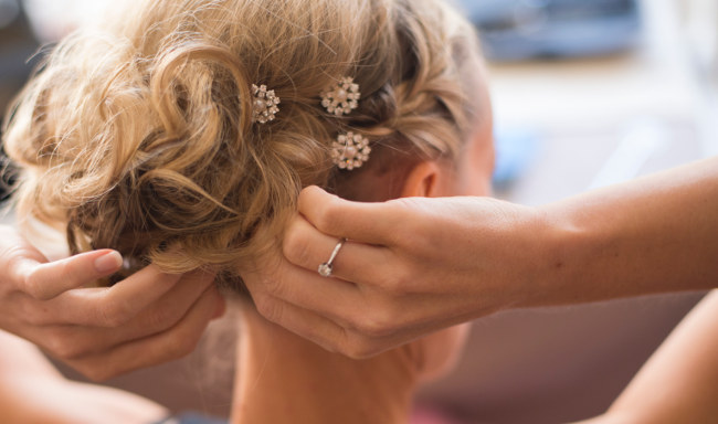 A bride adjusting jeweled pins holding her hair up