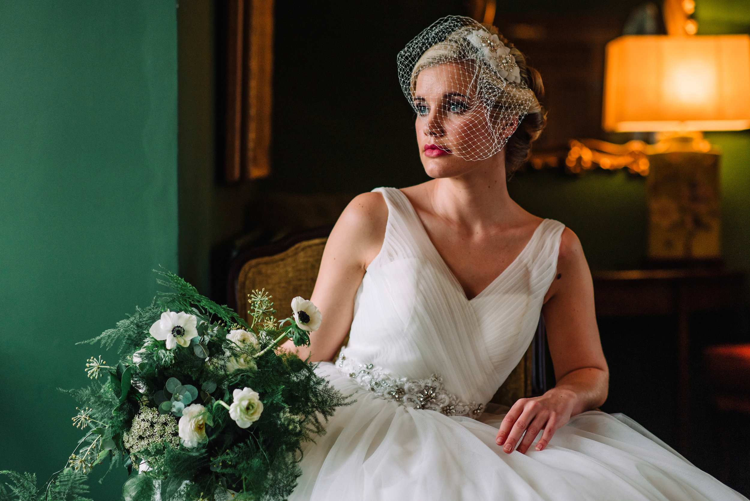 Bride sitting in chair holding a bouquet of flowers and wearing a white wedding dress