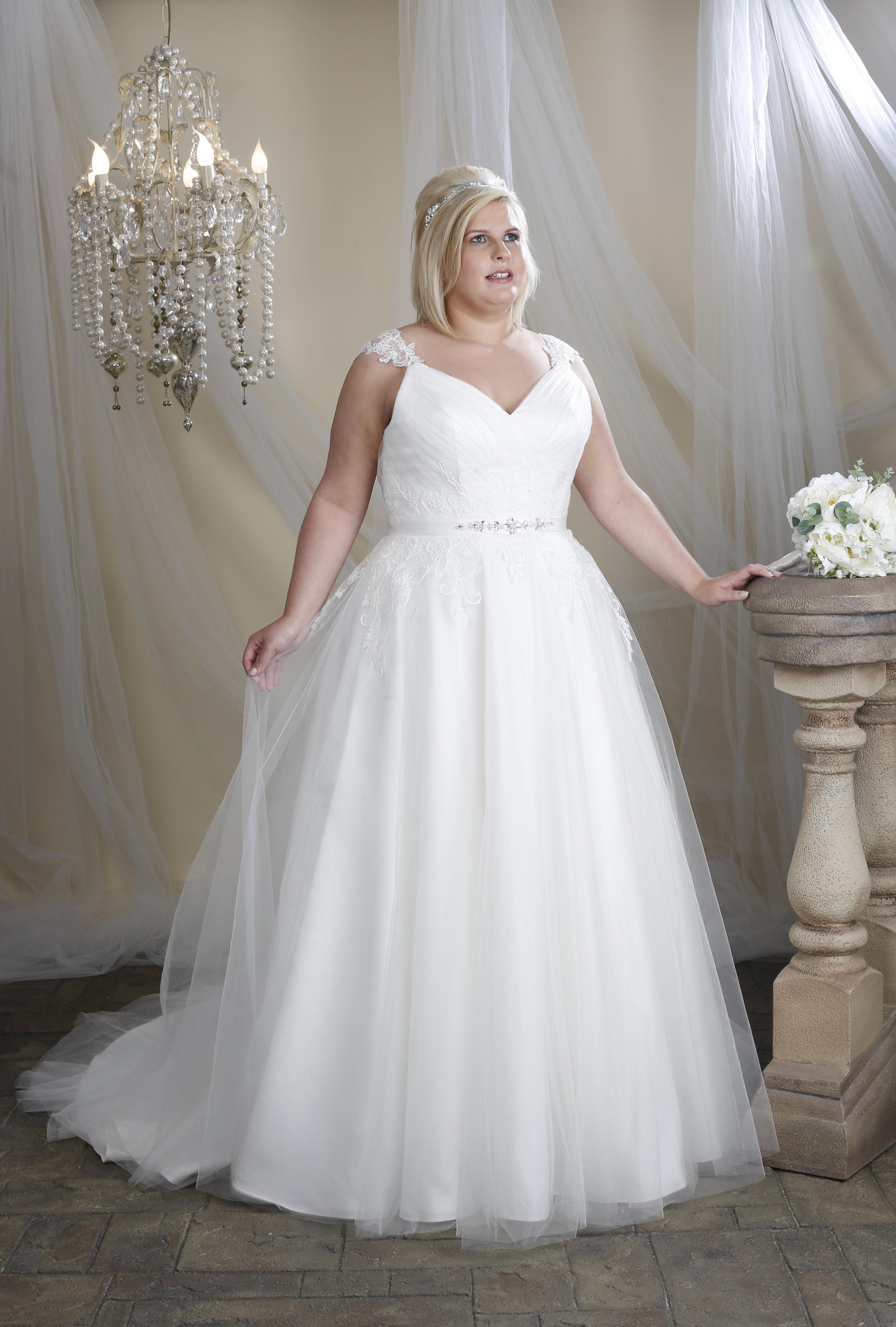 A curvy model wearing a plus size Hilary Morgan wedding dress