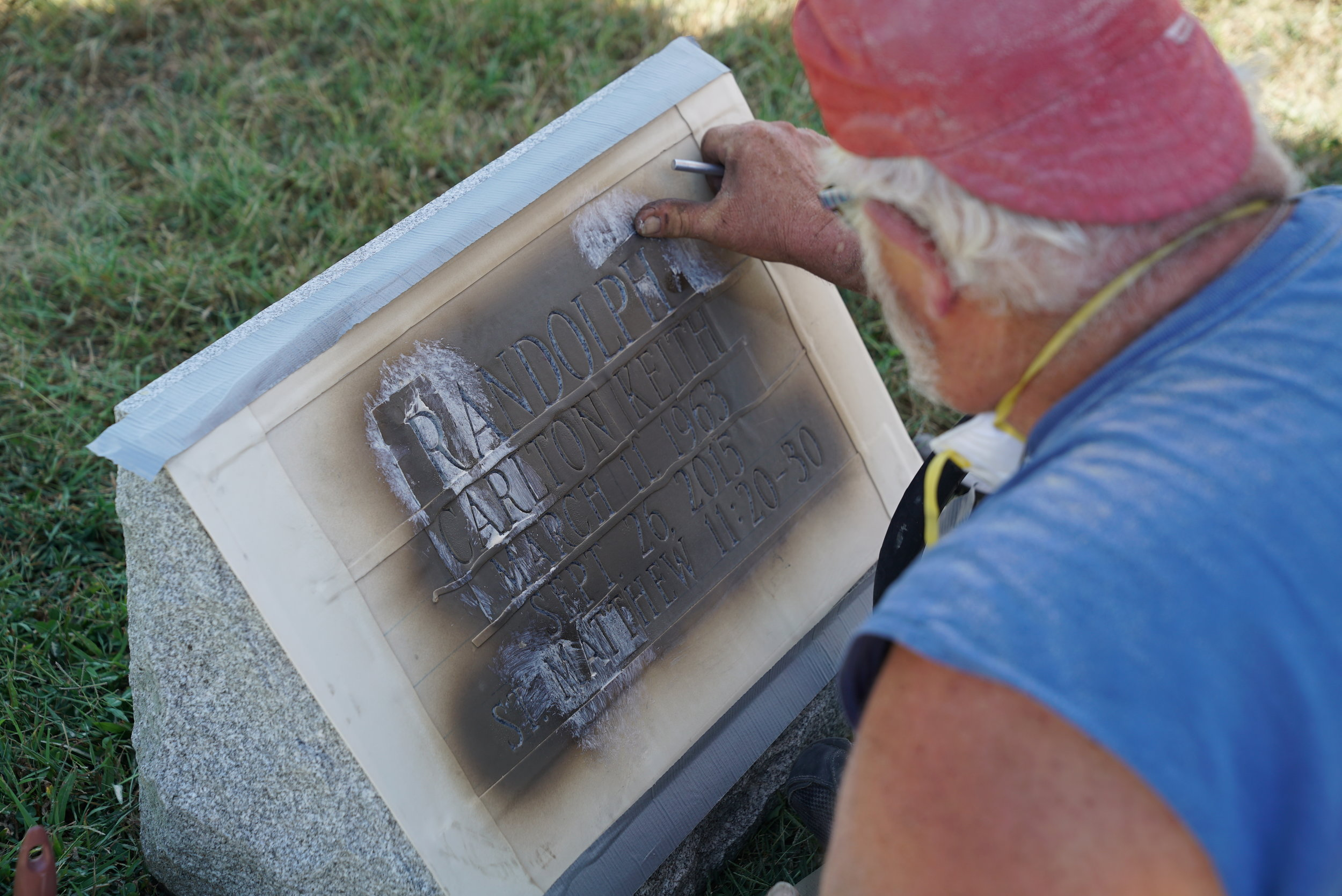 A tradesman doing an inscription job on a slant marker. In metropolitan Philadelphia, expect headstone inscription work to take 90 days.  (Not many people do this sort of work.)